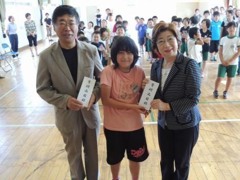 守屋会長から目録をいただいた小本小学校児童代表と小野小本中学校長。