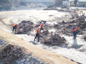 河川敷で手掛かりを探す消防団員たち
